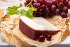 Traditional Spanish cheese, Murcian wine cheese from goat milk w. Traditional Spanish cheese, one piece of Murcian wine cheese from goat milk with rind washed in stock images
