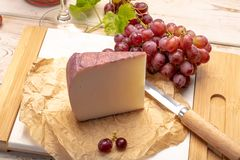 Traditional Spanish cheese, Murcian wine cheese from goat milk w. Traditional Spanish cheese, one piece of Murcian wine cheese from goat milk with rind washed in stock photography