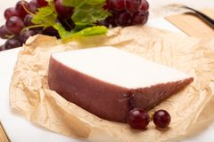 Traditional Spanish cheese, Murcian wine cheese from goat milk w. Traditional Spanish cheese, one piece of Murcian wine cheese from goat milk with rind washed in royalty free stock photos