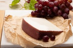 Traditional Spanish cheese, Murcian wine cheese from goat milk w. Traditional Spanish cheese, one piece of Murcian wine cheese from goat milk with rind washed in stock photos