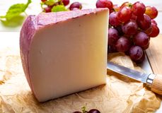 Traditional Spanish cheese, Murcian wine cheese from goat milk w. Traditional Spanish cheese, one piece of Murcian wine cheese from goat milk with rind washed in royalty free stock photography