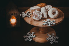 Traditional Spanish Christmas cookies polvorones, nevaditos and mantecados on a wood cake stand, burning candle Royalty Free Stock Images