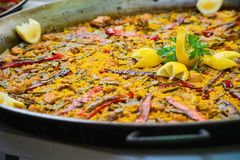 Traditional spanish dish paella with prawns and mussels. Closeup of a traditional tasty spanish dish paella served with meat, lemon and vegetables Stock Photos