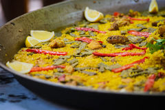 Traditional spanish dish paella with prawns and mussels. Closeup of a traditional tasty spanish dish paella served with meat, lemon and vegetables Stock Image