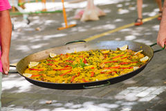Traditional spanish dish paella with prawns and mussels. Closeup of two men holding cooked traditional spanish dish paella in their hands Royalty Free Stock Images