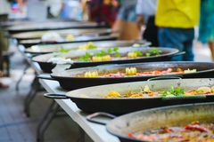 Traditional spanish dish paella with prawns and mussels. Row of a traditional tasty spanish dish paella served with meat, garlic and vegetables on a table Stock Image