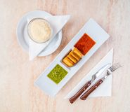 Traditional Spanish food. Green and red mojo sauce with fried bread and parmesan cheese stock image