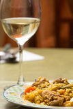 Traditional Spanish food, rice with rabbit and wine glass Stock Photography