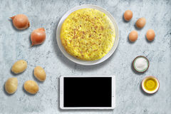 Traditional spanish omelette on marble background with ingredients and tablet mockup. Stock Photo