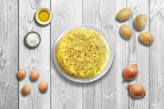 Traditional spanish omelette on marble wooden background with ingredients. Stock Image