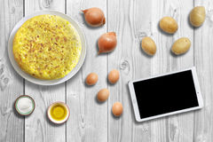 Traditional spanish omelette on wooden background with ingredients and tablet mockup. Royalty Free Stock Images