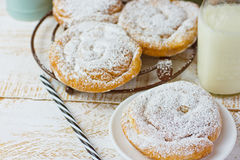 Traditional Spanish or Philippine pastry ensaimada. Powdered, on cooling rack and plate. Glass of milk Stock Images