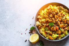 Traditional spanish seafood paella in pan rice, peas, shrimps, mussels, squid on light grey concrete background. Top Stock Images