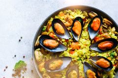 Traditional spanish seafood paella in pan rice, peas, shrimps, mussels, squid on light grey concrete background. Top. View, copyspace Stock Images