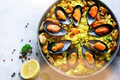 Traditional spanish seafood paella in pan rice, peas, shrimps, mussels, squid on light grey concrete background. Top. View, copyspace Royalty Free Stock Images
