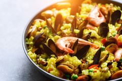 Traditional spanish seafood paella in pan rice, peas, shrimps, mussels, squid on light grey concrete background. Top Royalty Free Stock Photography