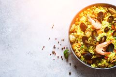 Traditional spanish seafood paella in pan rice, peas, shrimps, mussels, squid on light grey concrete background. Top Stock Photos
