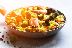 Traditional spanish seafood paella in pan rice, peas, shrimps, mussels, squid on light grey concrete background. Top. View, copyspace Stock Photography
