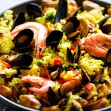 Traditional spanish seafood paella in pan rice, peas, shrimps, mussels, squid on light grey concrete background. Top. View, copyspace Stock Photo