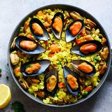 Traditional spanish seafood paella in pan rice, peas, shrimps, mussels, squid on light grey concrete background. Top. View, copyspace Royalty Free Stock Photos