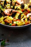 Traditional spanish seafood paella in pan rice, peas, shrimps, mussels, squid on light grey concrete background. Top. View, copyspace Royalty Free Stock Photo