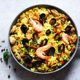 Traditional spanish seafood paella in pan rice, peas, shrimps, mussels, squid on light grey concrete background. Top. View, copyspace Stock Image