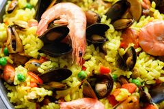 Traditional spanish seafood paella in pan rice, peas, shrimps, mussels, squid on light grey concrete background. Top. View, copyspace Royalty Free Stock Image