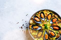 Traditional spanish seafood paella in pan rice, peas, shrimps, mussels, squid on light grey concrete background. Top Royalty Free Stock Photo