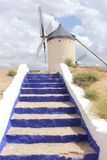 Picturesque Spanish mill with blue stairs along Don Quichot route,Consuegra, Spain. Traditional ancient Spanish windmill with blue painted steps in Castile La Stock Image