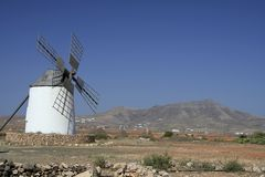 Traditional Spanish Windmill, left of frame. Blue sky and a hill. Taken in fuerteventura (Canary Isles) but is also typical of windmills in La Mancha region stock images