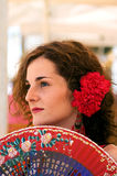 Traditional Spanish Woman with Red Fan. Spanish girl with carnations in hair and a traditional red polka dot feria dress gazes towards the sky with a penisve stock photo