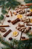 Traditional spices for bakery cinnamon, anise stars, ginger, dried oranges on the wooden background with Christmas tree branches. Royalty Free Stock Photos