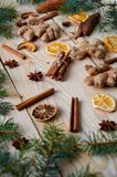 Traditional spices cinnamon, anise stars, ginger, dried oranges on the wooden background with Christmas tree branches still life. Stock Images