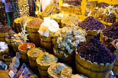 Traditional spices market - pots and wooden tubs stand in row with colorful tea, spices, fruits, roots, flowers. Street bazaar. Colorful spices powders and herbs Stock Photos