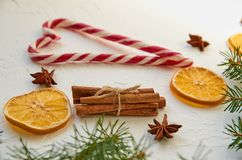 Traditional spices for mulled wine on the white concrete table: anise stars, cinnamon sticks, dried oranges. Heart of candy cones Royalty Free Stock Images