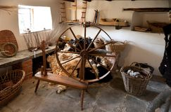Traditional spinning wheel. Traditional workshop with spinning wheel, fleece and baskets, England Stock Photos