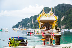 Traditional spirit house in Thailand san phra phum against turquoise sea water, ships and mountains.Phi-Phi Stock Photography