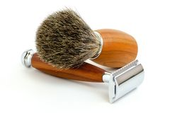 Traditional razor with hairy shaving brush isolated in white. Traditional steel razor with hairy shaving brush isolated in white stock photo