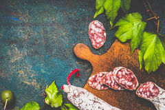 Traditional stick of salami sausage on rustic cutting board on dark vintage background, top view Stock Photos
