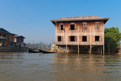 Traditional stilts house and boat in water under blue sky Stock Photography