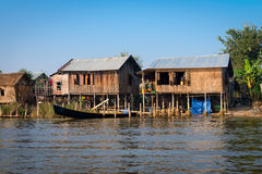 Traditional stilts house and long boats in water under blue sky Stock Image