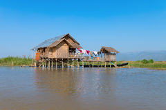 Traditional stilts house in water under blue sky Royalty Free Stock Photography