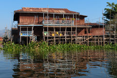 Traditional stilts house in water under blue sky Stock Image