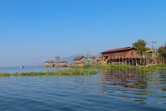Traditional stilts house in water under blue sky Stock Images