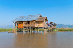 Traditional stilts house in water under blue sky Royalty Free Stock Photos