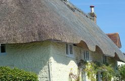 Traditional stone cottage with reed thatched roof. Traditional reed thatched roof of a stone built cottage in a small Sussex village in the UK. An insurance stock photo
