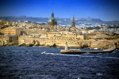 Entering the port of Valletta,Malta. Traditional stone made buildings,light house and fotress in Valletta,Malta with a blue sky,clouds and coastline Royalty Free Stock Images
