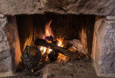 Traditional stone-made fireplace with burning wood Stock Photo