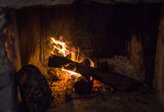 Traditional stone-made fireplace with burning wood Stock Photos
