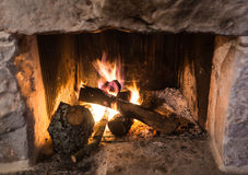 Traditional stone-made fireplace with burning wood Stock Image